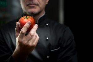31527309 - confident elegant chef holding a delicious tomato on dark background.